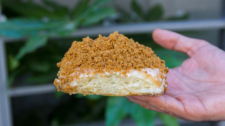 ROLI ROLLS cinnamon roll con frosting de queso crema y topping de cookie polvoreada