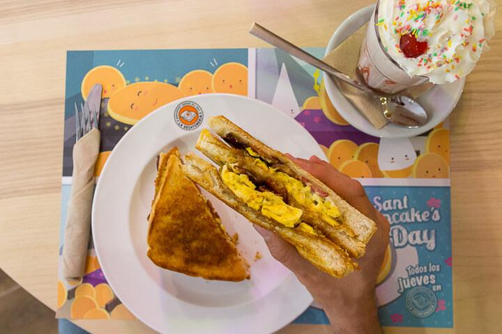 LA DESAYUNERIA MADRID Grilled Sandwich Sant Antoni con huevo revuelto, crispy bacon, cheddar y salsa ranchera
